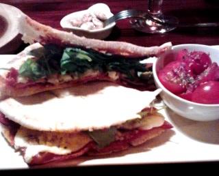 Pita rellena con queso halloumi, bacon, tomate, rúcula y olivas